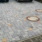 Zweifarbiges Pflaster und unterschiedlich große Steine - Abwasserdeckel eingearbeitet