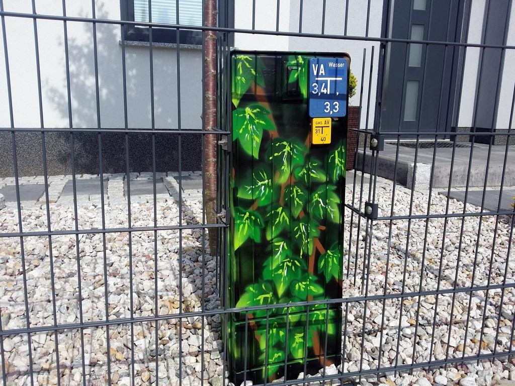 Stromkasten mit Efeu-Graffiti