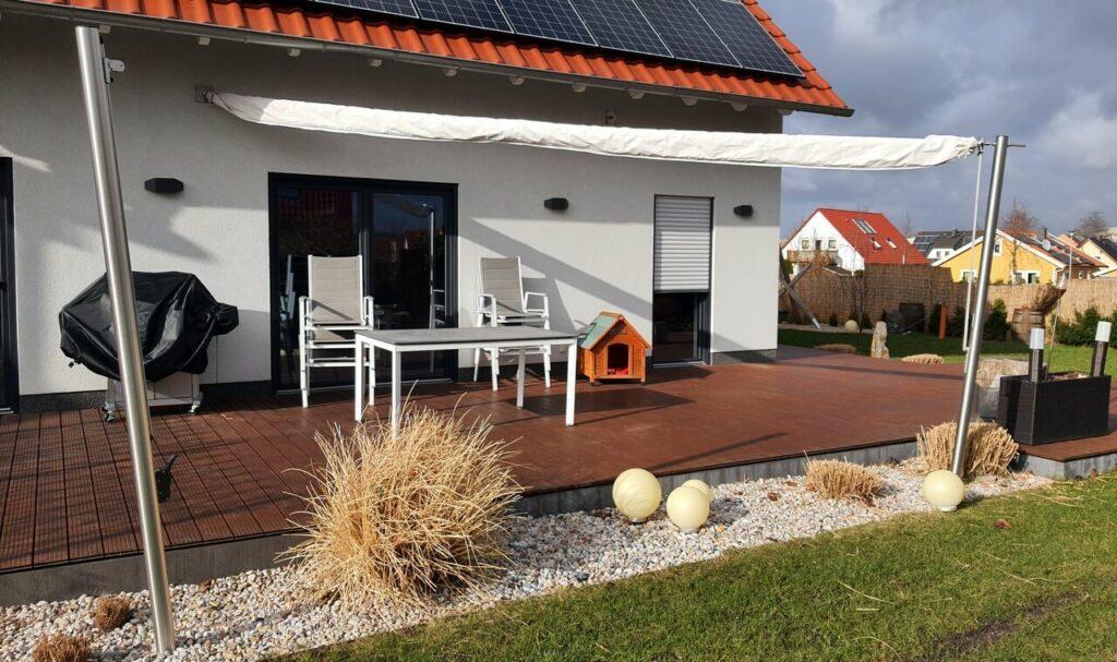 Blick auf Terrasse mit Sonnensegel und Schutzhülle